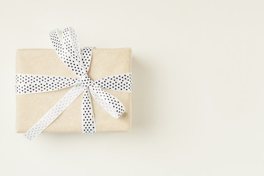 Wrapped gift box with ribbon bow on a white background, copy space