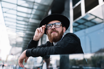 Portrait of successful businessman standing on the street near business center. Young bearded hipster wearing stylish clothes corrects glasses, he waiting  taxi.