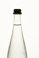 Transparent bottle with dew. Close up. Bottleenck with cap, white isolated background.