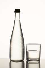 Transparent glass bottle with water and cup. Glass bottle and cup with dew isolated on white.