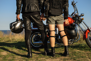 Portrait of a young couple in leather clothes are holding hands. Bikers on motorcycle background