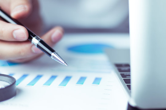 Business people use pen to point graphs to analyze company data and statistics from the chart.