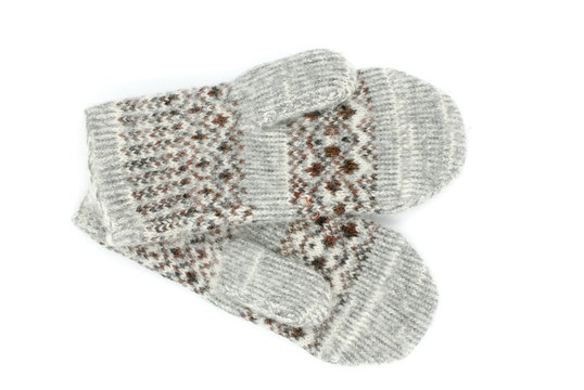 Warm wool gray mittens with a pattern is on a white background
