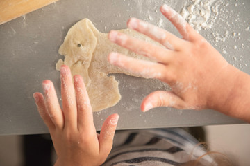 the child rolls with a rolling pin dough, cooks food on the gray desktop with the scattered flour