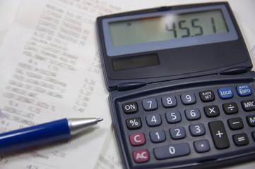 Calculator and pen to control daily expenses