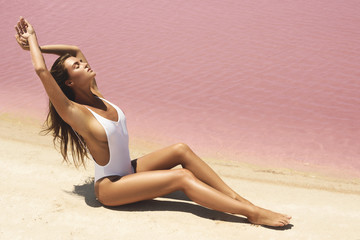 Sexy woman lying on the beach with pink water