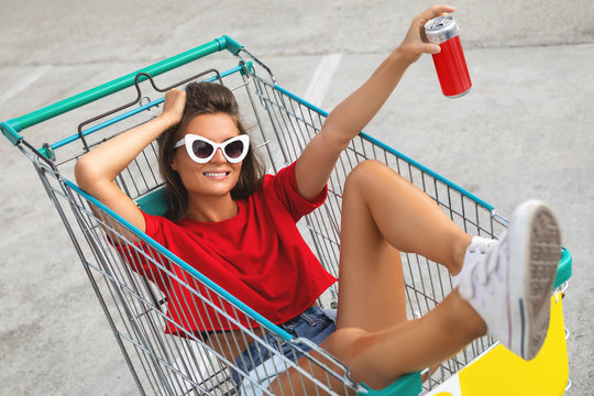 Woman sitting inside a shopping cart with soft drink on the parking of supermarket