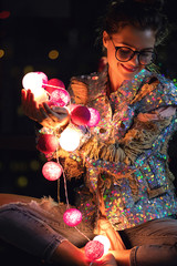 Happy woman wearing glowing jacket with sequins is holding light balls in her hands