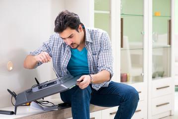 Young man husband repairing tv at home