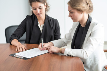 Two business women signing a document