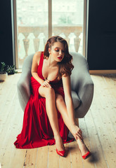 gorgeous red-haired young woman sexually touches her bare leg, showing the neckline. in a long scarlet expensive long luxurious dress and red high-heeled shoes in a room with window to the floor