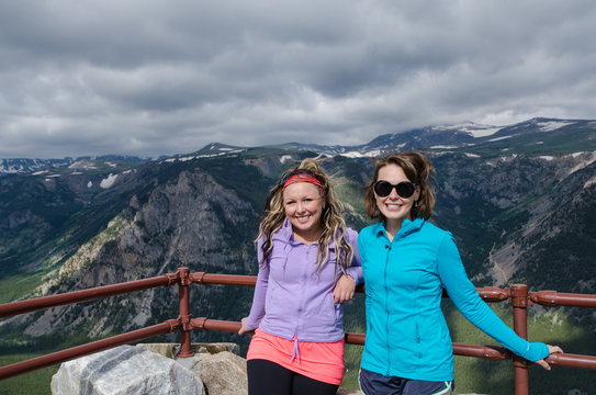 Two female friends (20s) pose together at an overlook along Montana Beartooth Pass Highway in the Rocky Mountains