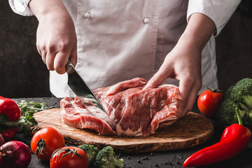 Chef Butcher cutting pork meat with knife on kitchen, cooking food