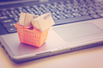 Online shopping / retail ecommerce and delivery service concept : Small boxes in an orange shopping basket on a laptop, depicts consumers purchase or order products from suppliers or digital stores.