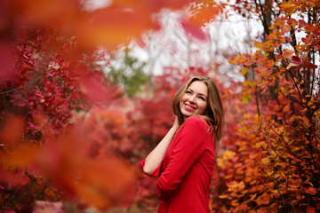 Beautiful cheerful girl in a red dress in the autumn park