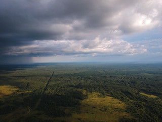 view of the road to a huge cloud with rain from the height of the quadrocopter, around the road forests and fields