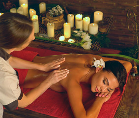 Deep tissue massage treatment in Ayurveda of woman in spa salon. Top view girl on candles background treats problem back. Luxary Filipino therapy interior with working masseuse.