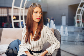A young beautiful brown-haired girl dressed in a striped fashionable dress is sitting in a summer outdoor cafe and is waiting for her order and her friends or her boyfriend