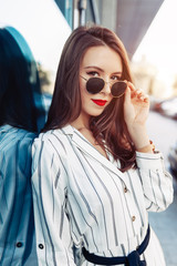Summer sunny lifestyle fashion portrait of young stylish hipster woman with sunglasses walking on the street, wearing cute trendy outfit enjoy her weekends, travel alone