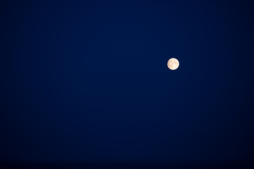 A full little moon on a blue sky