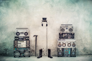 Retro old design ghetto blaster boombox radio cassette tape recorders, headphones, cylinder hat, leather boots, walking stick cane front concrete street wall. Vintage style filtered conceptual photo