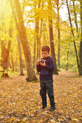 Creative child, kid photographer (a little boy) with a camera taking pictures of colorful autumn forest