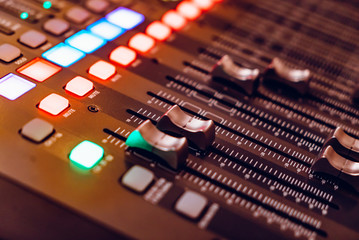 mixing console for recording with faders and bright buttons is in the building. Close-up