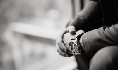 black and white photo of a businessman in a suit with a watch on his hand. Blurred background. Close-up