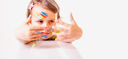 Art, creative and happiness childhood concept. Colorful painted hands in a beautiful young girl.