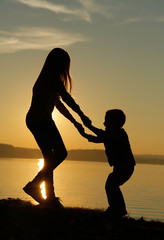 Children at sunset by the sea playing different games