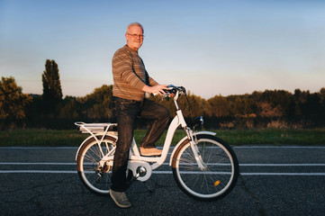 Old man cyclist on the e-bike or electric white bicycle on the nature background. Active pension. Travel. Sport.
