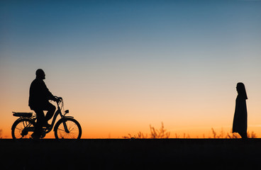 Male cyclist on the e-bike or electric bicycle on the sunset background. Silhouette of the man in profile. Active pension. Travel. Sport.