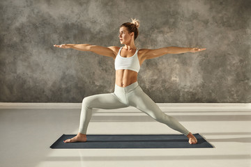Sideways full image of attractive muscular young woman practicing hatha yoga at gym, standing barefooted on mat in Virabhadrasana 2 or Warrior Two pose, having concentrated facial expression