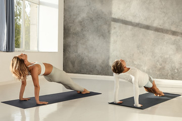 Indoor picture of fit blonde woman and muscular man practicing yoga asanas in modern gym together, doing backwards plank to get strong arms and torso. Healthy lifestyle, activity and sports concept