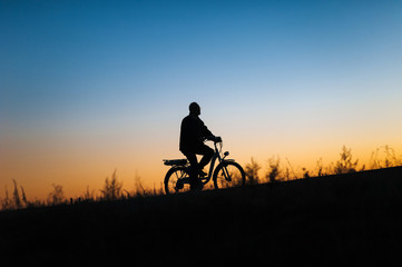 Male cyclist on the e-bike or electric bicycle on the sunset background riding up the hill. Silhouette of the old man in profile. Active pension. Travel. Sport.