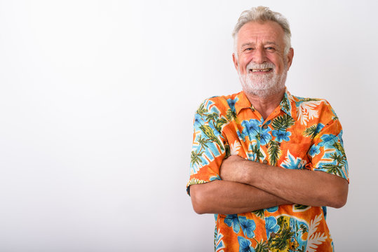 Studio shot of happy senior bearded tourist man smiling with arm