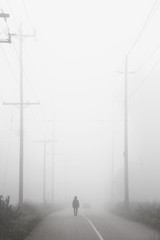 Heavy fog along a paved trail; single person walking into the fog