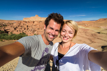 Active happy couple taking selfie on travel at Ait Benhaddou,fortified city, kasbah or ksar, along the former caravan route between Sahara and Marrakesh in present day Morocco.