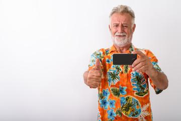 Studio shot of happy senior bearded tourist man smiling while gi