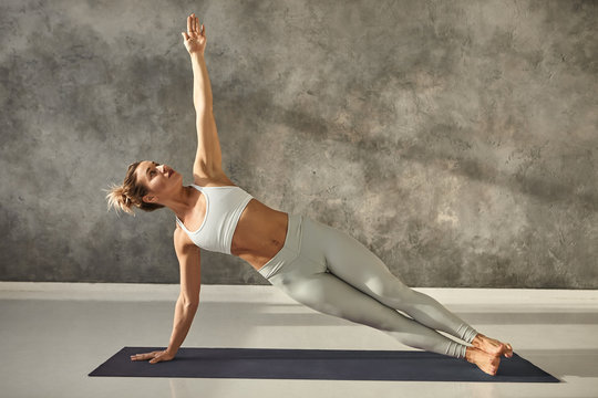 Pretty girl wearing leggings and short top standing in side plank on one hand at gym, training body core and balance, strengthening abs muscles. Attractive female doing planking bodyweight exercise