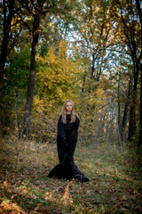 Halloween witch in the woods, a young girl in a witch's suit