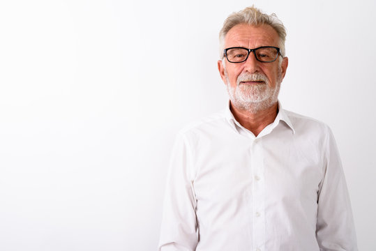Studio shot of happy senior bearded man smiling with eyeglasses