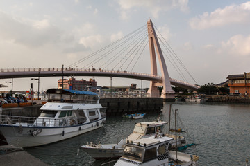 View from Fisherman's Wharf located along the coast of Tamsui District, New Taipei City Taiwan. Harbor with boats and sunset with calm water, ocean boats and buildings in the background.