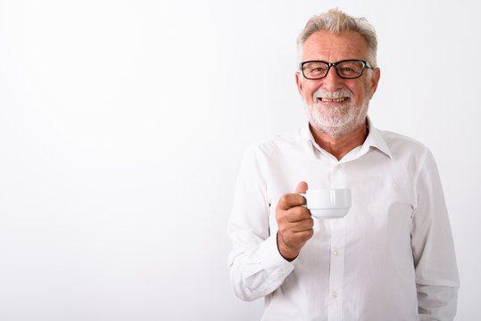 Studio shot of happy senior bearded man smiling while holding co