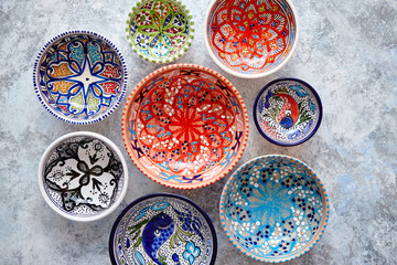 Collection of empty moroccan colorful decorative ceramic bowls. Composition captured from top view, flat lay. Placed on grey stone background.