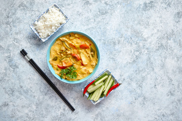 Traditional Chinese or Thai chicken yellow curry with vegetables served with steamed rice cucomber...