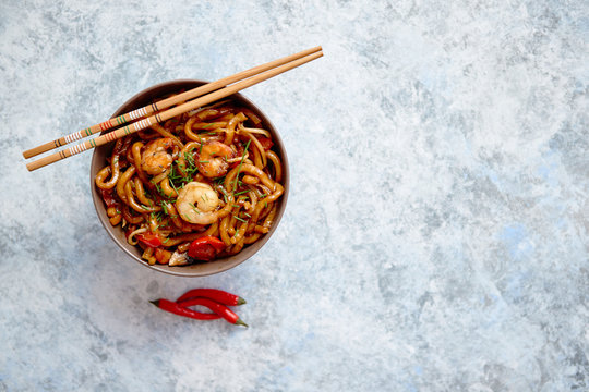 Traditional asian udon stir-fry noodles with shrimp in bowl and chopsticks. Fresh chilli pepers on side. Placed on bright stone background with copy space.