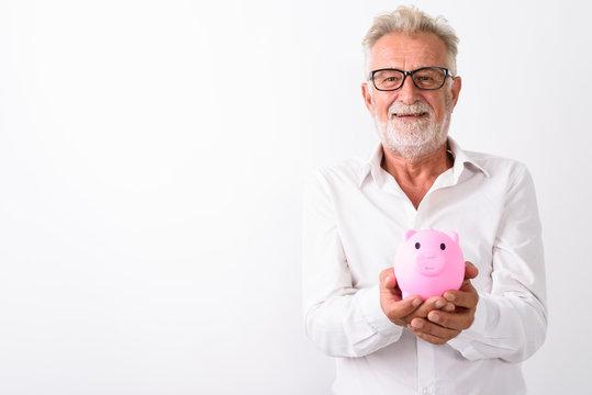 Studio shot of happy senior bearded man smiling while holding pi