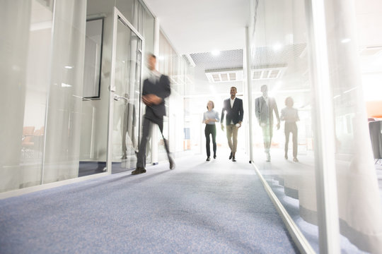 Blurred motion of modern business people crossing illuminated office corridor while hurrying to their workplaces, corporate company