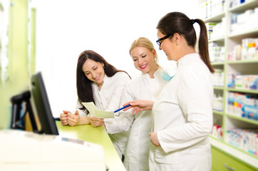 Three young adult female pharmacist talking on work